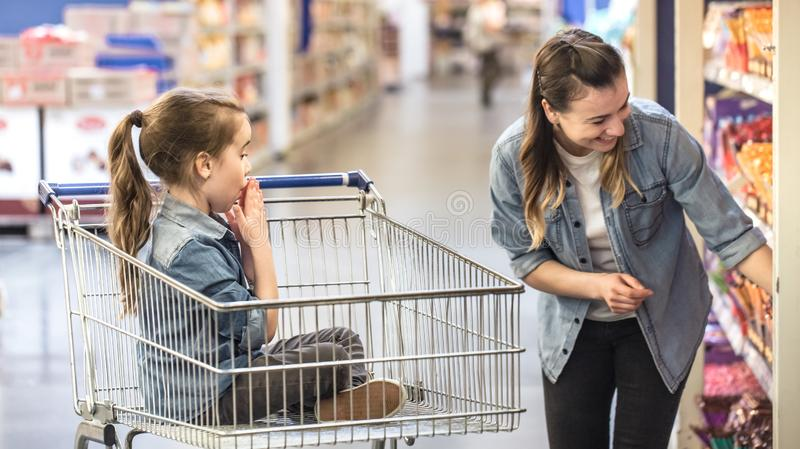 Mother and daughter shopping in supermarket choosing products stock image