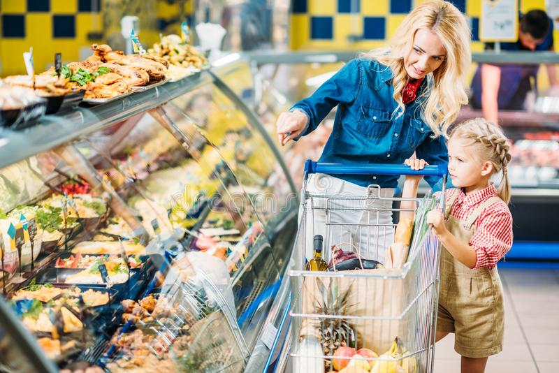 mother and daughter with shopping trolley choosing food while shopping stock images