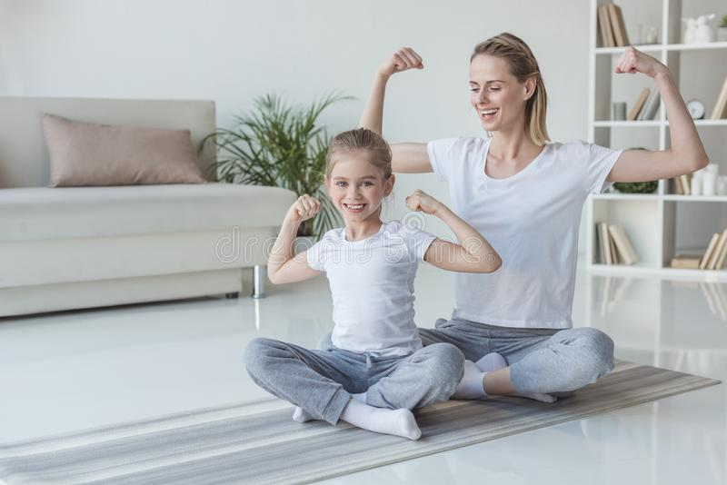 mother and daughter showing muscles stock image