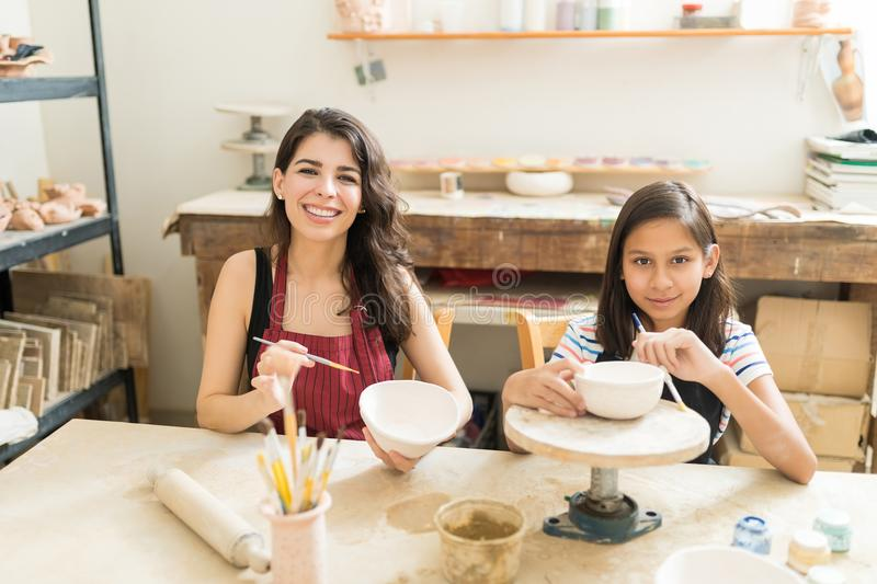 Mother And Daughter Showing Their Innovative Pottery Painting Te. Portrait of mother and daughter showing their innovative pottery painting techniques at table stock image