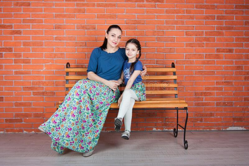 Mother and daughter  in similar clothes hug and sit on the bench with cross legs stock photos