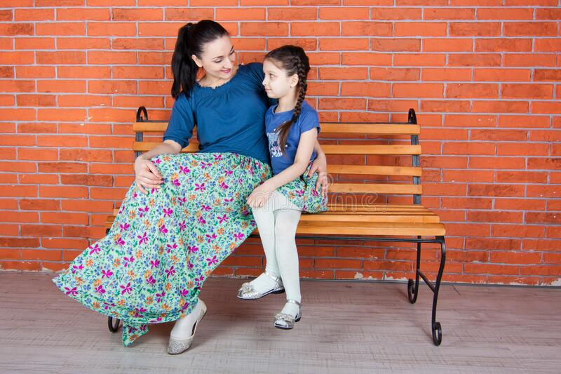 Mother and daughter  in similar clothes sit on the bench in front of red brick wall. royalty free stock image