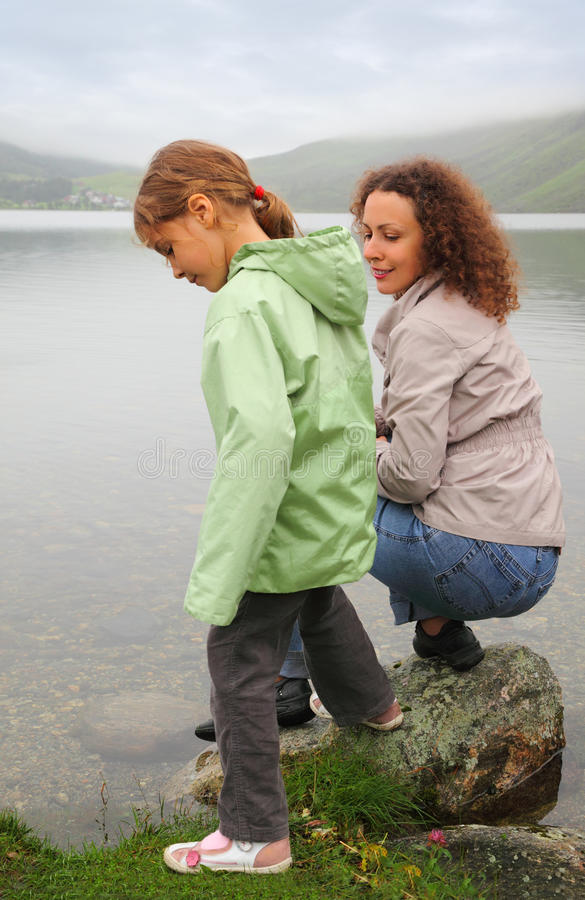 Download Mother With Daughter Sit At Background Of Lake Stock Photos - Image: 26087003