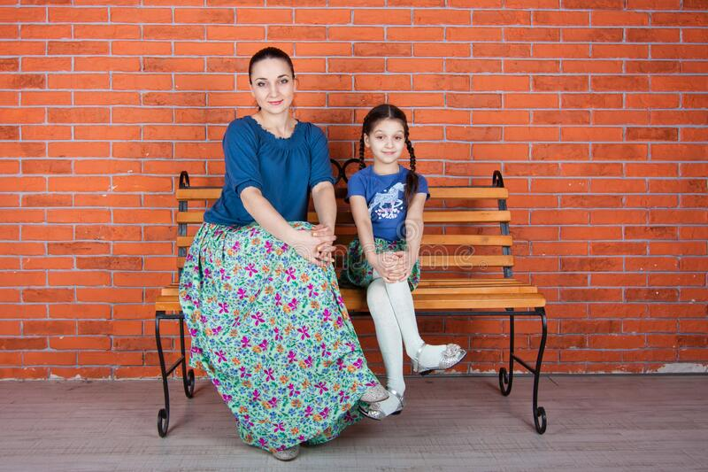 Mother and daughter and sit on the bench in front of red brick wall. royalty free stock image