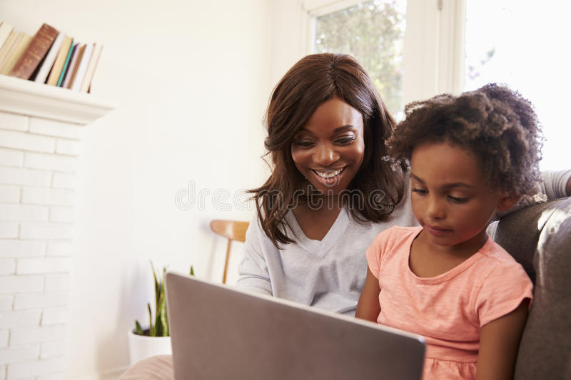 Mother And Daughter Sit On Sofa At Home Using Laptop royalty free stock images