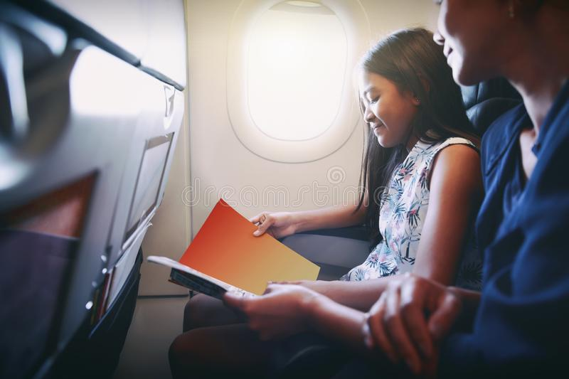 Mother with daughter sit on their place in airplane. Economy class and read a magazine stock images