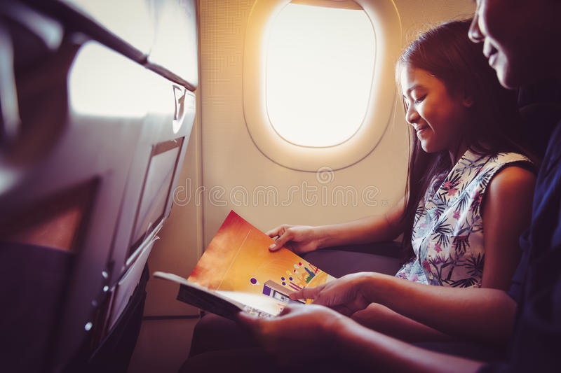 Mother with daughter sit on their place in airplane. Economy class and read a magazine royalty free stock image