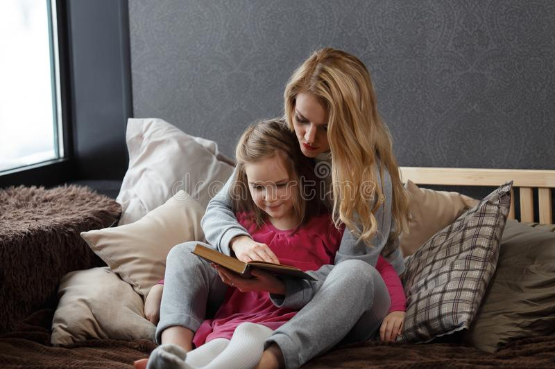 Mother and daughter sitting on the bed in an embrace and reading a book royalty free stock image