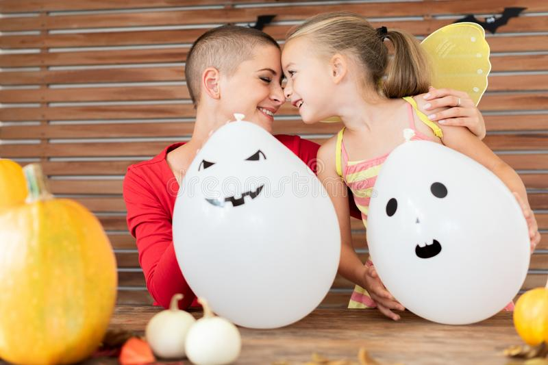 Mother and daughter sitting behind a table in halloween decorated room, playing with ghost character balloons. royalty free stock photos