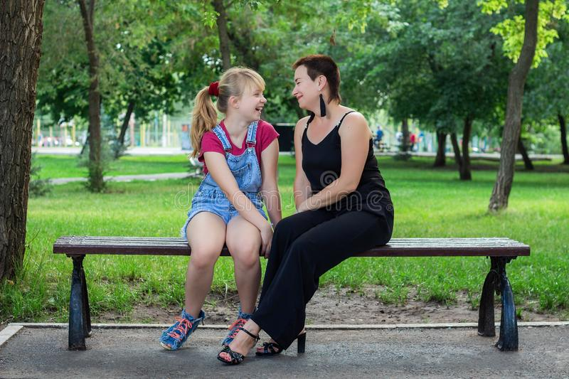 Mother and daughter sitting on a bench in the Park stock photo