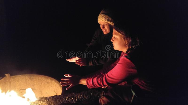 Mother and Daughter sitting by a campfire on a cold night. Location shot of a single mom and ten year old daughter on a camping trip at night by the fire royalty free stock image