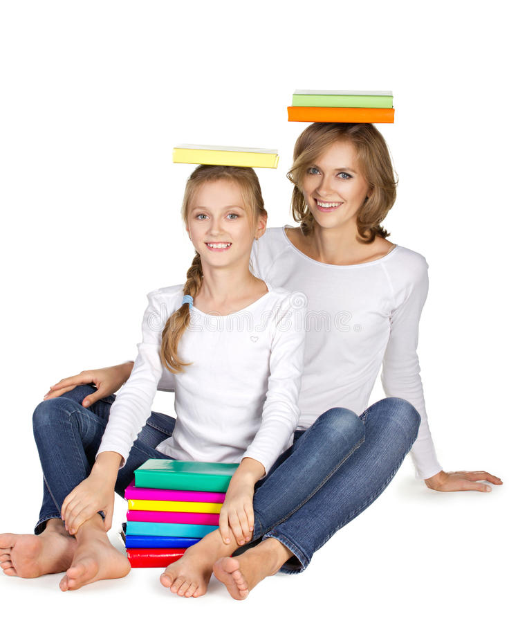Mother and daughter sitting on the floor with books on heard royalty free stock image