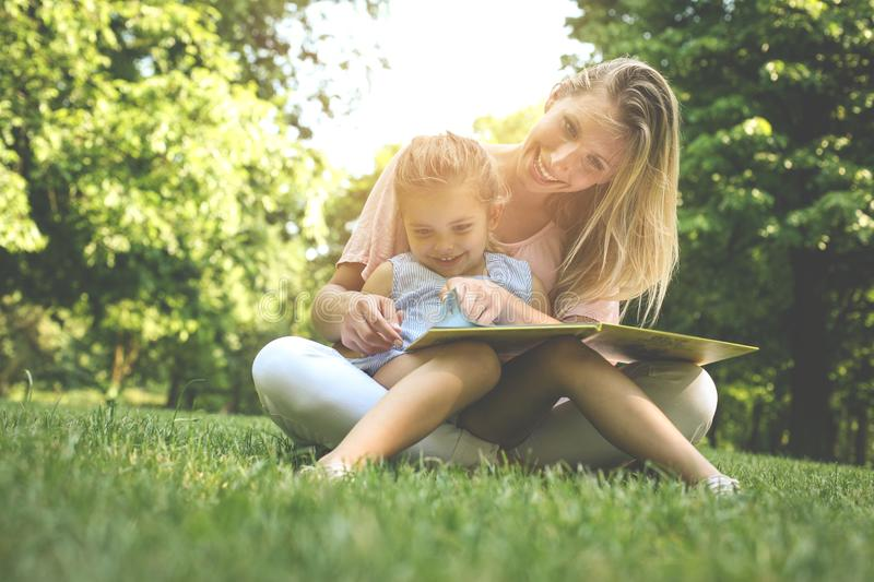 Mother and daughter sitting on green grass and reading book together. Little girl sitting on mother lap. stock photography