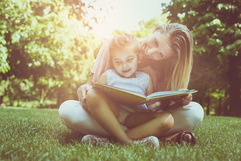 Mother and daughter sitting on green grass and reading book together. Little girl sitting on mother lap. stock image