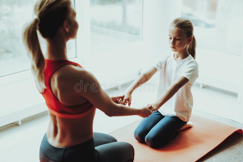 Mother And Daughter Sitting On Gym Carpet At Home. Mother And Daughter Sitting On Gym Carpet. Yoga Concept. Meditation Pose. Active Lifestyle. Hold Each Other stock photos
