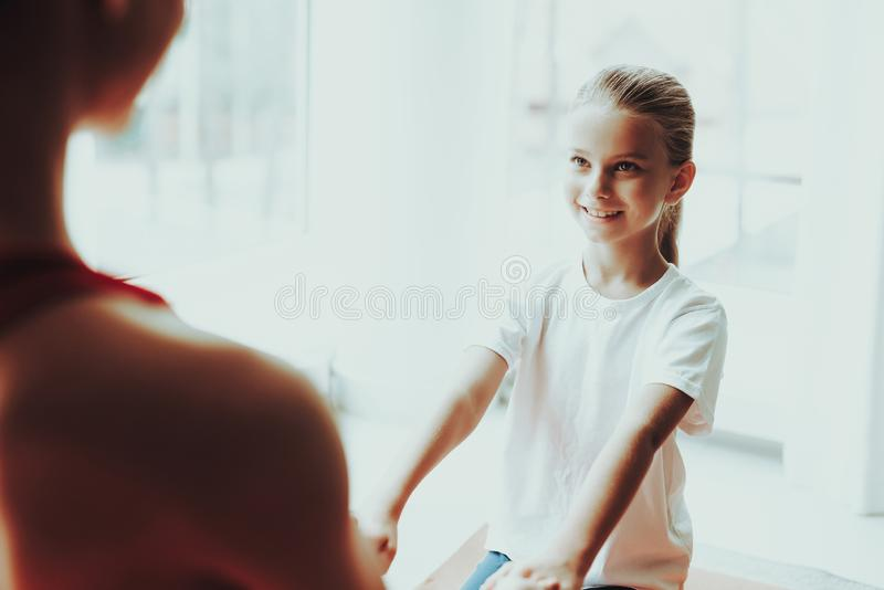 Mother And Daughter Sitting On Gym Carpet At Home. Mother And Daughter Sitting On Gym Carpet. Yoga Concept. Meditation Pose. Active Lifestyle. Hold Each Other royalty free stock photography