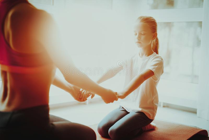 Mother And Daughter Sitting On Gym Carpet At Home. Mother And Daughter Sitting On Gym Carpet. Yoga Concept. Meditation Pose. Active Lifestyle. Hold Each Other royalty free stock images
