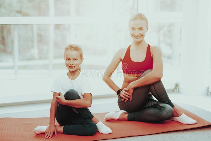 Mother And Daughter Sitting On Gym Carpet At Home. royalty free stock images