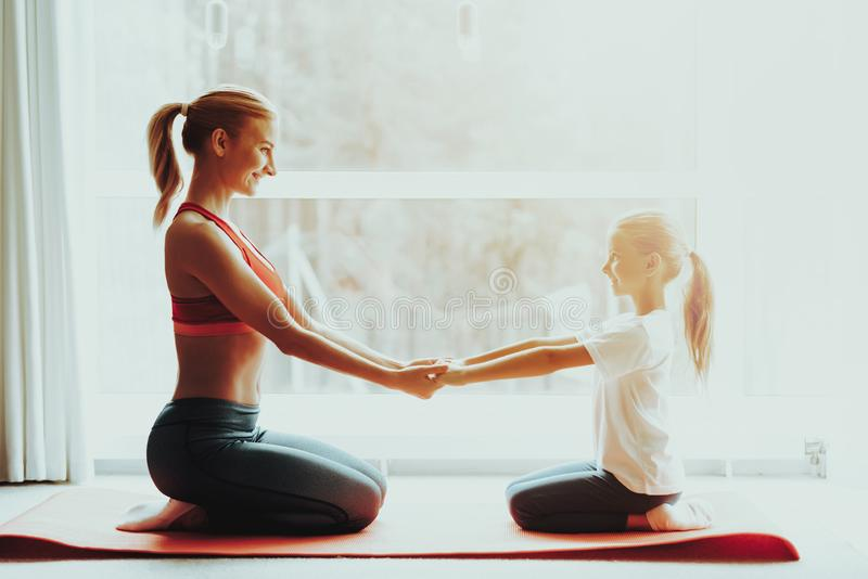Mother And Daughter Sitting On Gym Carpet At Home. Mother And Daughter Sitting On Gym Carpet. Yoga Concept. Meditation Pose. Active Lifestyle. Hold Each Other stock images