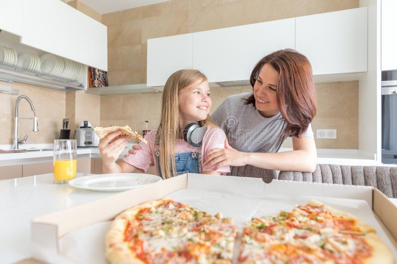 Mother and daughter sitting in the kitchen, eating pizza and having fun. Focus on daughter stock photos