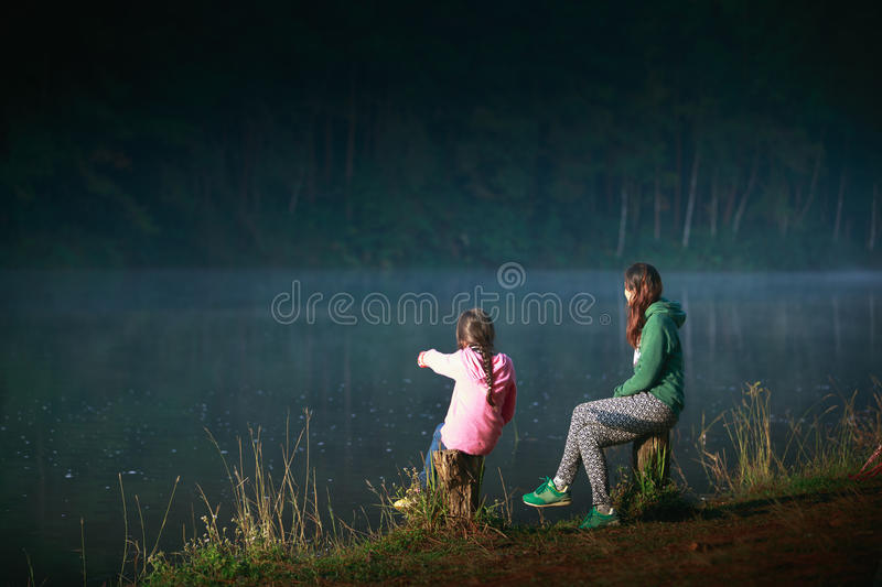 Mother and daughter. Sitting near river in the forest royalty free stock photos