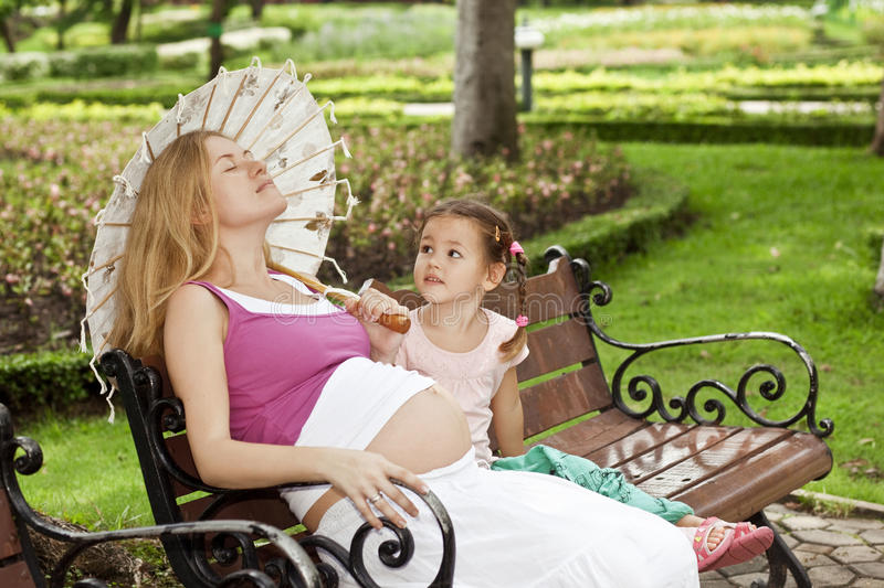 Mother and daughter sitting on a park bench royalty free stock photos