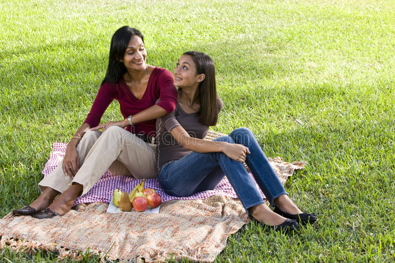 Mother and daughter sitting on picnic blanket royalty free stock image