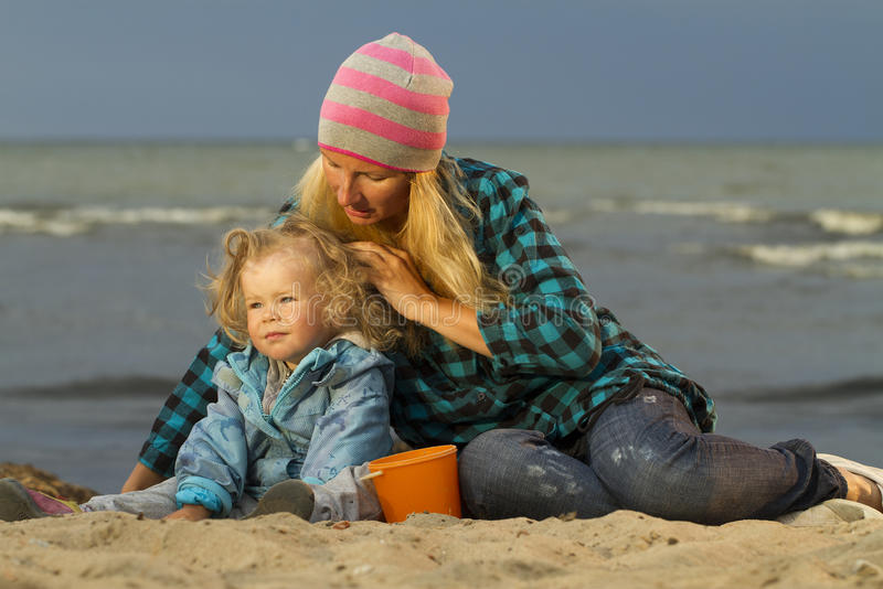 Mother and daughter sitting at the sea royalty free stock photos