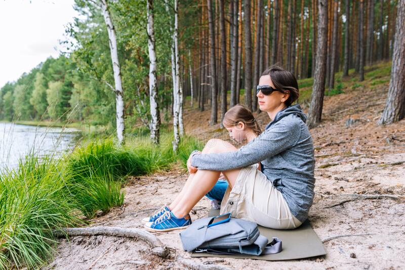 Mother and daughter sitting on the shore of the lake in the summer forest royalty free stock image