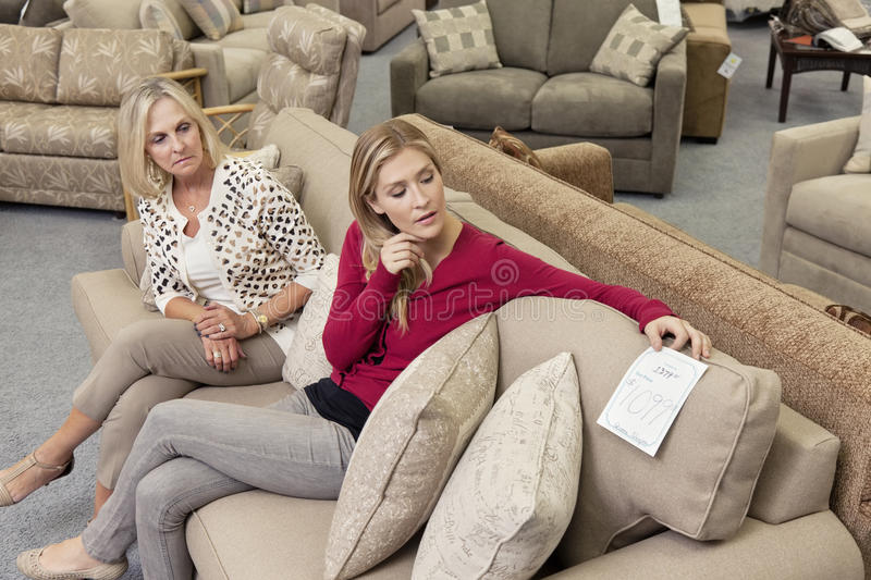 Download Mother And Daughter Sitting On Sofa While Looking At Price Tag In  Furniture Store Royalty