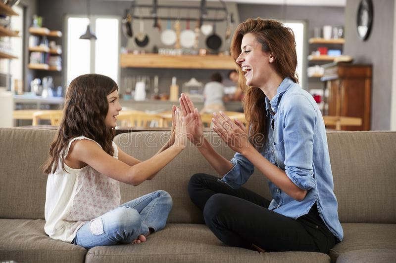 Mother And Daughter Sitting On Sofa Playing Clapping Game royalty free stock photos