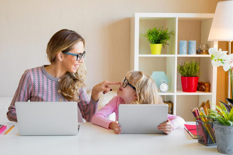 Mother and daughter sitting at table and using computers together. Working mom concept stock photos
