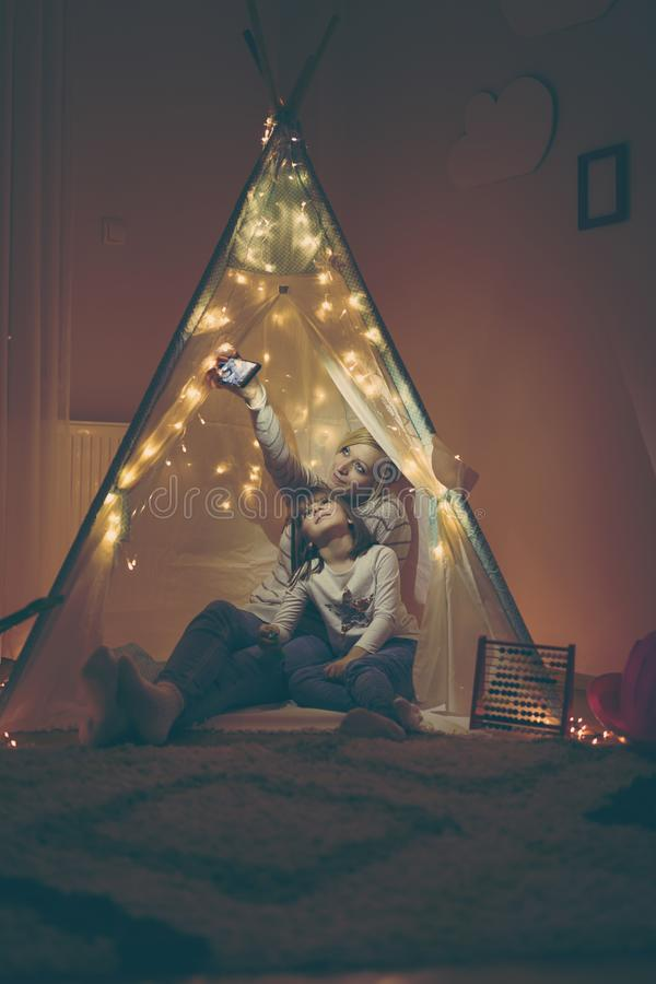 Mother and daughter taking selfie in a teepee stock images