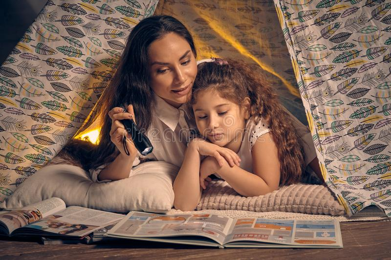 Mother and daughter are sitting in a teepee tent, reading stories with the flashlight. Happy family. royalty free stock photos