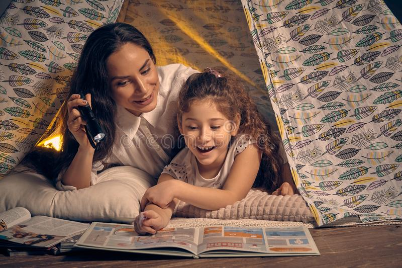 Mother and daughter are sitting in a teepee tent, reading stories with the flashlight. Happy family. Mother and her charming daughter are sitting in a teepee royalty free stock photography