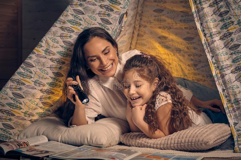 Mother and daughter are sitting in a teepee tent, reading stories with the flashlight. Happy family. Mother and daughter are sitting in a teepee tent, reading stock photography