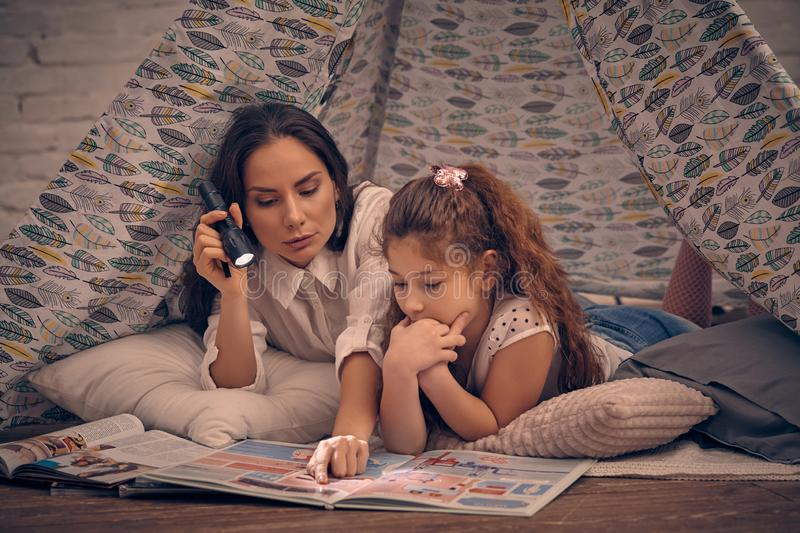 Mother and daughter are sitting in a teepee tent, reading stories with the flashlight. Happy family. stock photo
