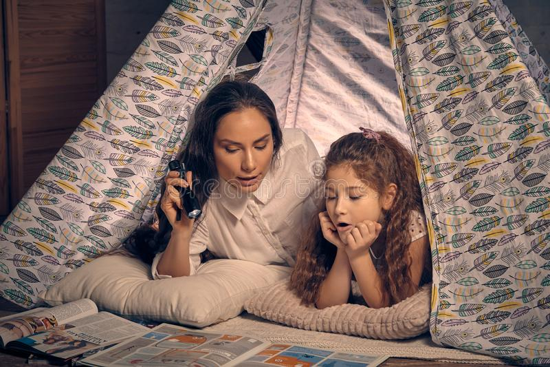 Mother and daughter are sitting in a teepee tent, reading stories with the flashlight. Happy family. They are reading together stock image