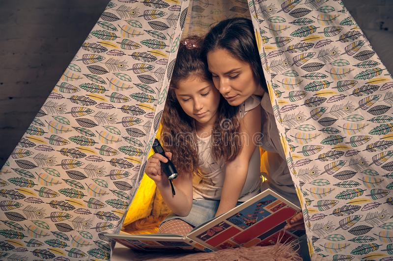 Mother and daughter are sitting in a teepee tent, reading stories with the flashlight. Happy family. Young mother and daughter are sitting in a teepee tent with stock photos