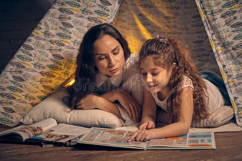 Mother and daughter are sitting in a teepee tent with some pillows and reading stories. Happy family. Mother and daughter are sitting in a teepee tent with some stock images