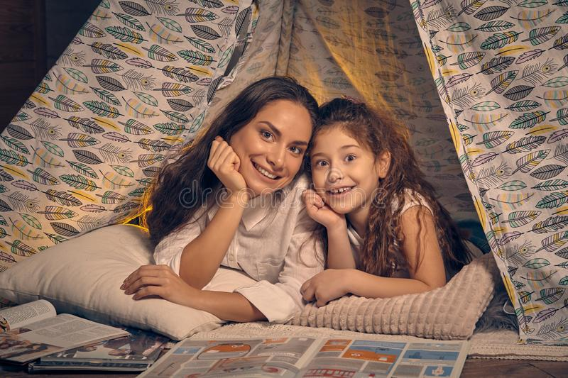 Mother and daughter are sitting in a teepee tent with some pillows and reading stories. Happy family. Mother and daughter are sitting in a teepee tent with some royalty free stock photos