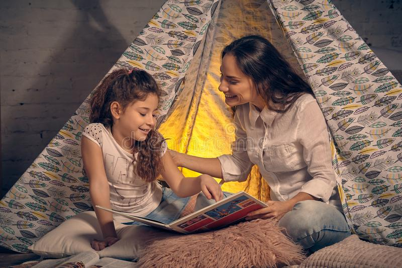 Mother and daughter are sitting in a teepee tent with some pillows and reading stories. Happy family. Mother and daughter are sitting in a teepee tent with some royalty free stock photo