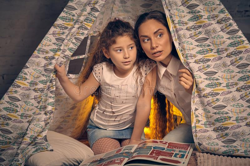 Mother and daughter are sitting in a teepee tent with some pillows and reading stories. Happy family. Young mother and her pretty daughter are sitting in a stock images
