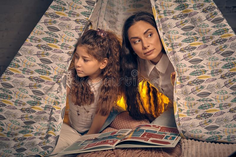 Mother and daughter are sitting in a teepee tent with some pillows and reading stories. Happy family. Young mother and her daughter are sitting in a teepee tent royalty free stock photo