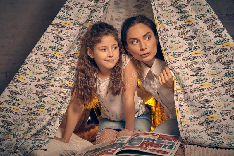 Mother and daughter are sitting in a teepee tent with some pillows and reading stories. Happy family. Young mother and her little daughter are sitting in a royalty free stock photo