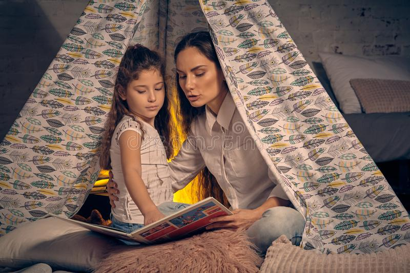 Mother and daughter are sitting in a teepee tent with some pillows and reading stories. Happy family. Mother and daughter are sitting in a teepee tent with some stock photography