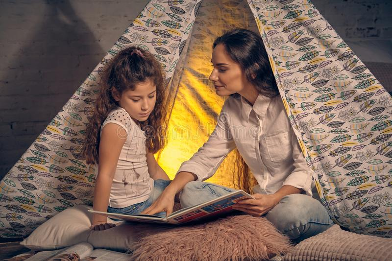 Mother and daughter are sitting in a teepee tent with some pillows and reading stories. Happy family. Mother and daughter are sitting in a teepee tent with some royalty free stock image