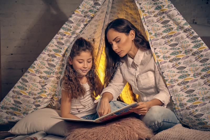 Mother and daughter are sitting in a teepee tent with some pillows and reading stories. Happy family. Mother and daughter are sitting in a teepee tent with some royalty free stock photography
