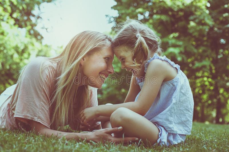 Mother and daughter sitting together on green grass. Mother and stock photo
