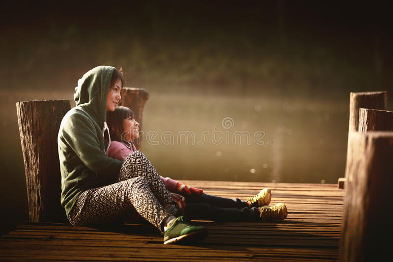Mother and daughter. Sitting on the wooden bridge near the river royalty free stock photos